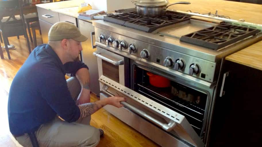 Liance Repairman Looking Into An Oven