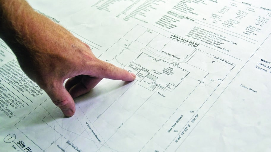 Beau Architect Examines Building Blueprints