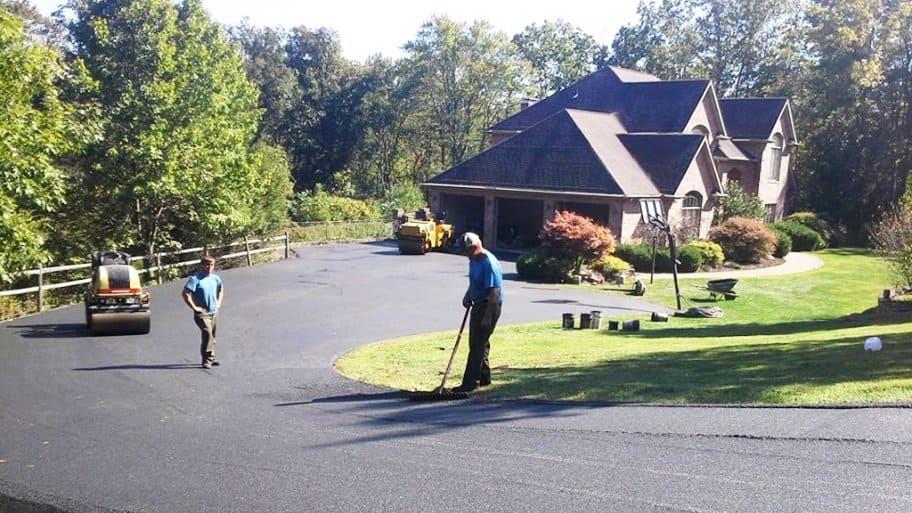 asphalt contractors paving a driveway