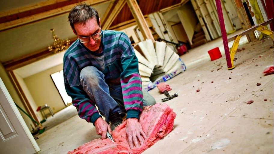 man cutting insulation