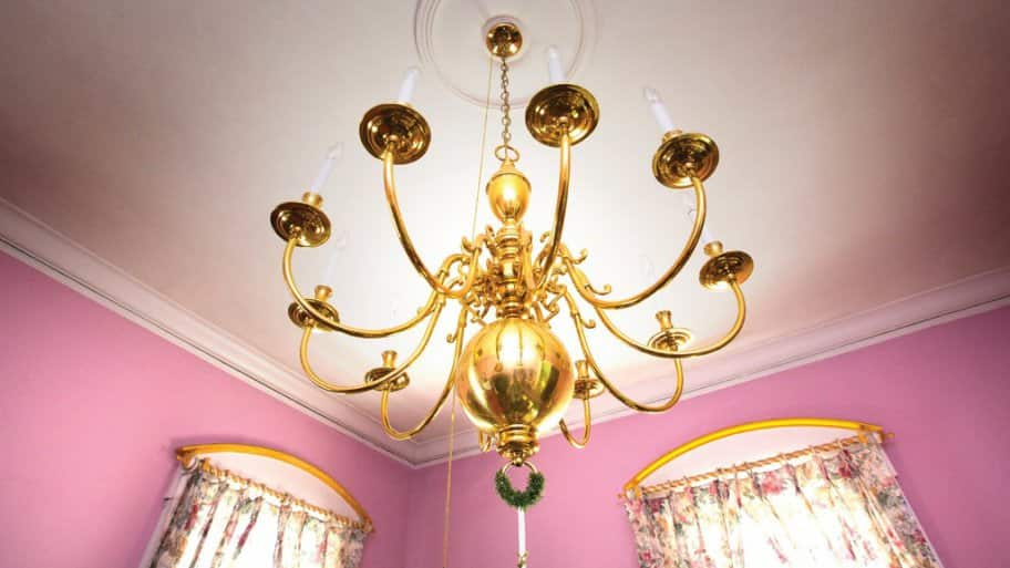 A gold chandelier in a bedroom with pink walls