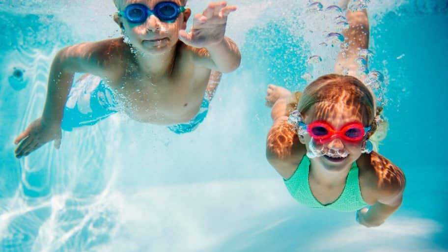 Two kids swimming underwater with goggles
