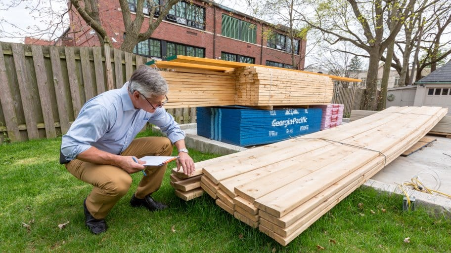 man inspecting wood on a new homebuilder site
