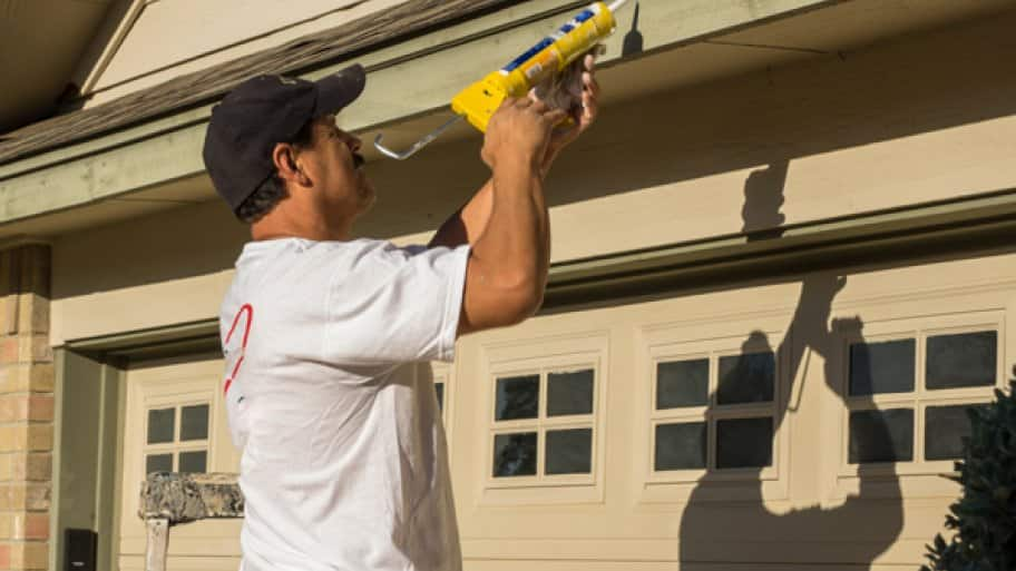 caulking gutter with caulk gun (Photo by Ray Mata)