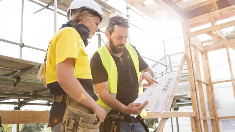 two homebuilders reviewing blueprints in a home being built