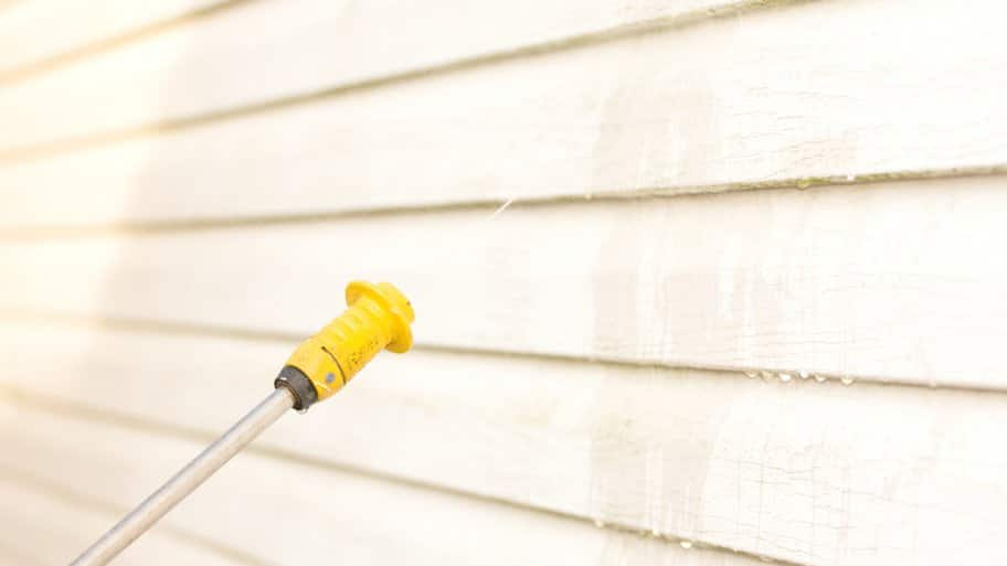 power washer nozzle spraying vinyl siding