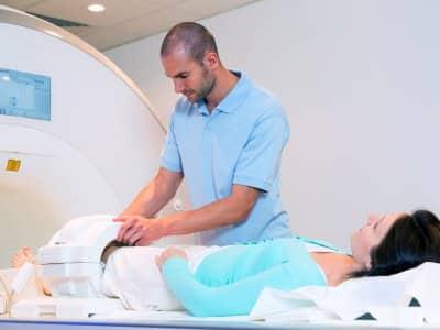 Medical technician preps woman knee for MRI