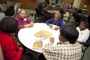 residet at a nursing home sit a table a make crafts.
