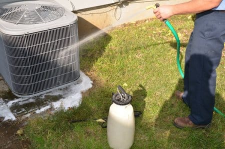 A/C unit being cleaned with soap and hose