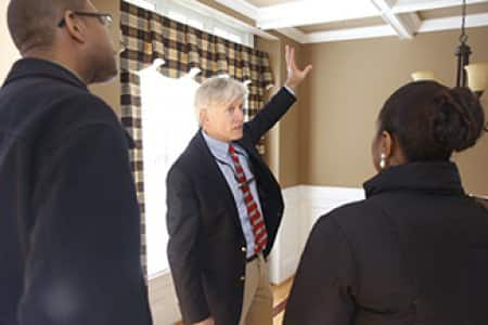Realtor David Jenkins shares his ideas about how to handle the ceiling color in the dining room with clients Antonio and Terri Harris during the final walkthrough of their new home in Raleigh, N.C. (Photo by Ray Black III)
