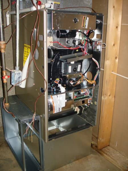 Installed furnace with front removed to show interior parts and components.
