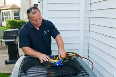 HVAC technician inspecting a/c unit