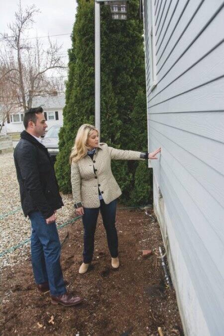 realtor and remodeler surveying side of home