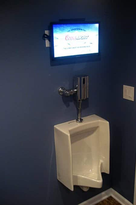 Putting a TV above the urinal in his man cave ensures no one will miss a second of the game. (Photo by Jim Brown)