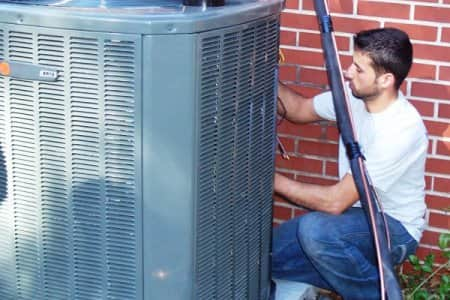 HVAC technician servicing air conditioner