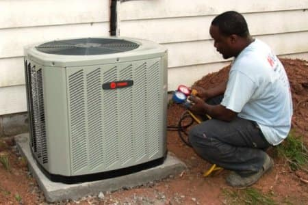 HVAC technician performs maintenance on an air conditioner