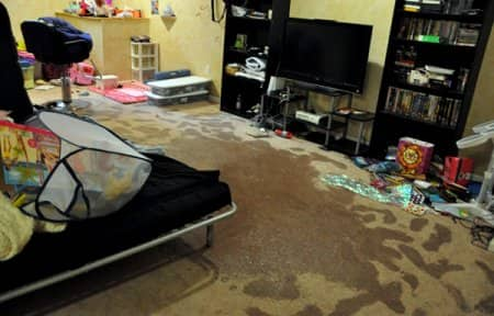 A flooded basement with wet carpet