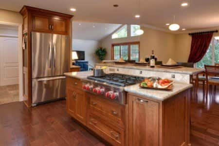 remodeled kitchen with wood floors, wood cabinets and light-colored countertops