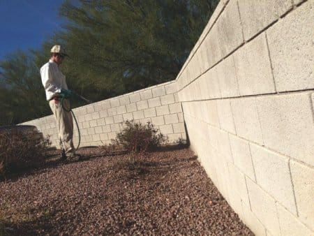 A tech creates a scorpion barrier outside of a Phoenix-area home. Scorpions often live in the cracks of concrete walls. (Photo by Bulwark Exterminating)