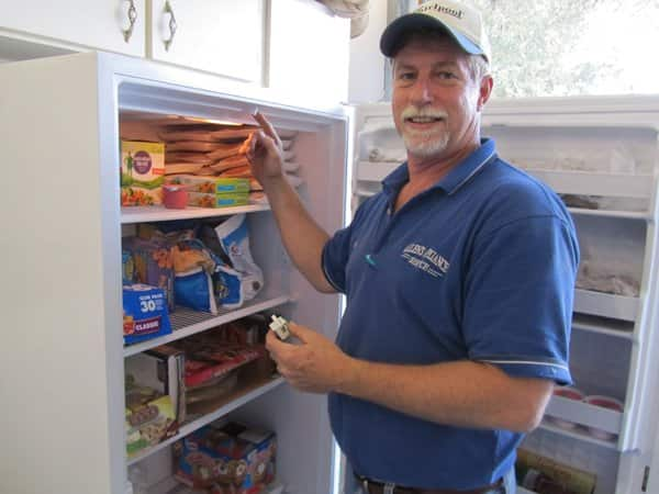 Allen's Appliance Service technician Jim Mims repairs a refrigerator. Mims is one of three service technicians at Allen's. (Photo courtesy of Walter Naumovitz)