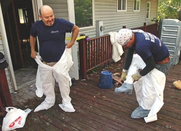 Mastercat remediation workers George Lopez, right, and Jorge Lopez put on protective suits before clearing the mold out of a Palatine, Ill., home. (Photo by Gilbert Boucher)