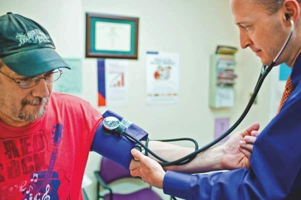 Dr. Brian Devine of Lakeside Family Physicians takes patient Michael Ferri's blood pressure, a preventive screening measure new health plans are required by law to cover.. (Photo courtesy of Jeremy Deal)