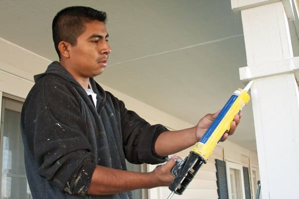 Jaime Rodriguez of Danny's Pro Painters caulks a house in The Westons neighborhood in Carmel before painting. Members rate Danny's prep work highly. (Photo by Lindy Keyser)