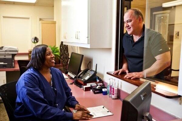 Patient Rick Lumadue talks with receptionist Regena Singleton before seeing Dr. Cyrus Peikari of Dallas. (Photo by Eric Priddy)