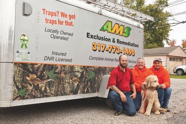 The Animal Management Systems team [from left] Tom Avery, certified wildlife technician; Cory McClung, owner with his dog and the business mascot, Oliver; and John Linbille, remediation technician. (Photo by Brandon Smith)