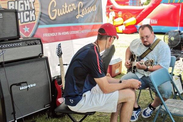 Jonathan Bobbe (right), owner of The Right Pick in Naperville, Ill., says an even mix of children and adults takes music lessons at his shop. (Photo courtesy of The Right Pick)