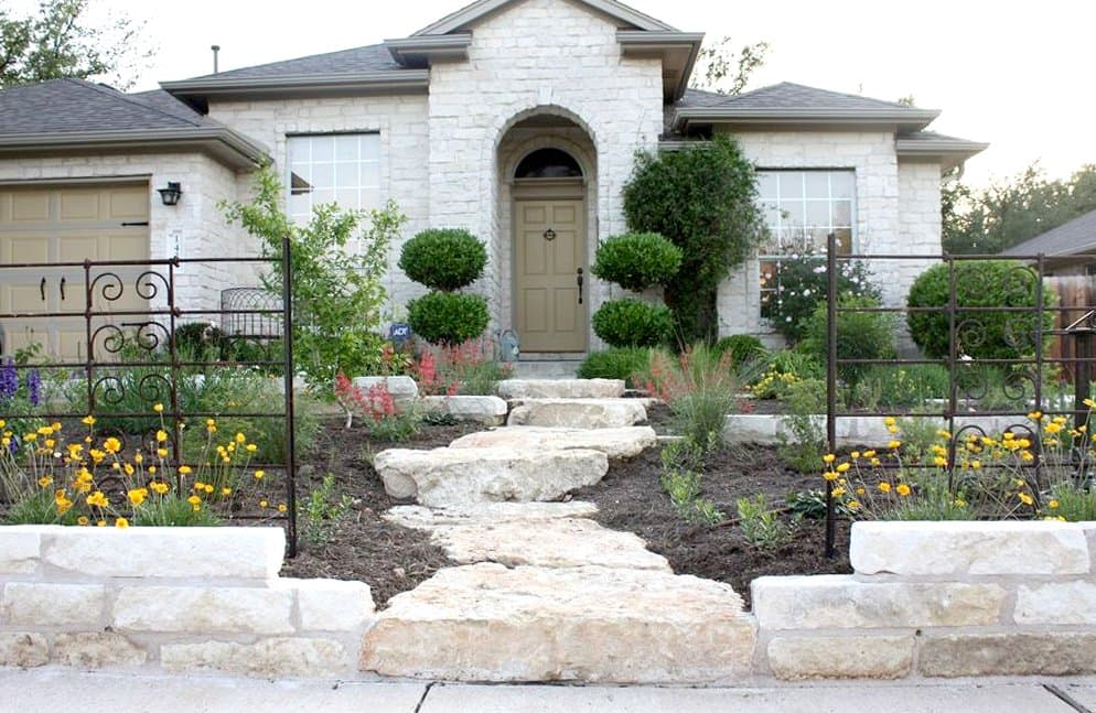 house exterior with shrubs and stone walkway
