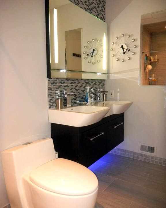 bathroom remodel with cabinets lit from underneath
