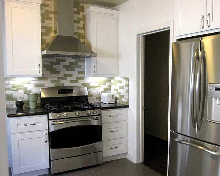 kitchen remodel with green tile backsplash and white cabinets