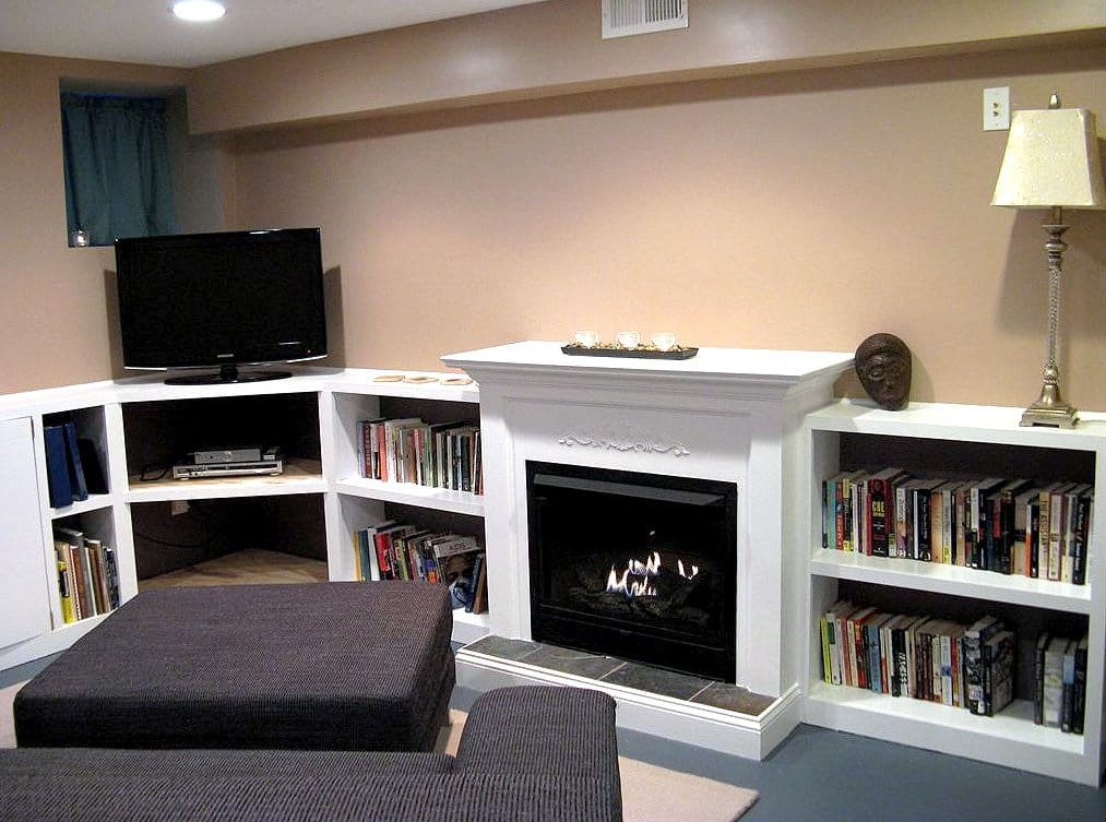 basement with fireplace and bookshelves
