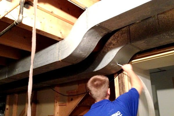 air duct technician using hose to clean air duct