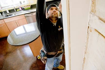 Pegasus employee Francisco Quijada measures a client's kitchen entryway for a renovation project that included recycled cork flooring and locally quarried tile countertops. (Photo by Mark Wilson)