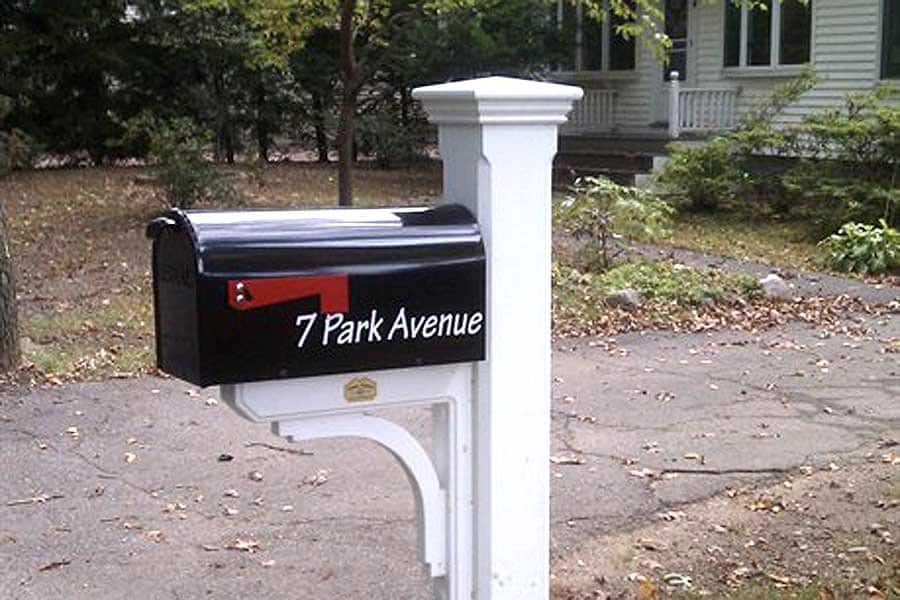 black mailbox on white wooden post