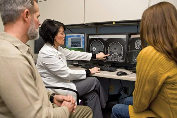 Dr. Stephanie Wagner speaks with Kelsey Stewart (left) and his wife, Kelly, about his recently removed brain tumor. (Photo by Brandon Smith)