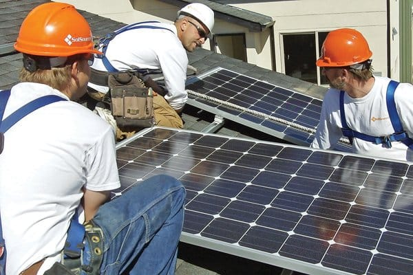 SolSource Inc. employees install solar panels on top of a homeowner's garage. (Photo courtesy of Seth Masia)
