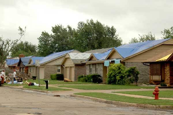 Damaged homes stand tarped, waiting for repairs following Monday's storm. (Photo by Katie Jacewicz)