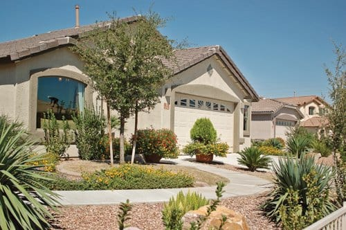 With plantings centered in the middle of the slightly sloping front yard, door and windows are visible from the street, yet roof run-off can be captured to grow the landscape.