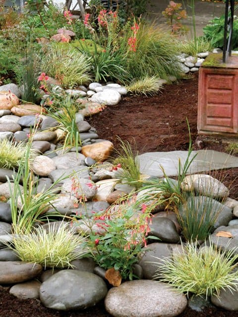 Photo courtesy of Rejuvenation Artisans Landscapes | Work done below the surface, including infiltration tests, adding gravel soil and installing silt traps and weed barriers, make swales beautiful and functional.