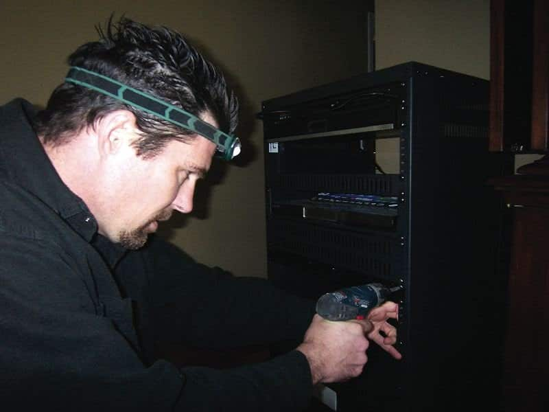 Rodney Cooper works on a client's new home entertainment system. Photos courtesy of Mary Jo Cooper