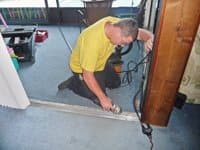 A Sliding Door Roller Replacement employee lays a new track in a client's home. Photo courtesy of Michelle Chamo