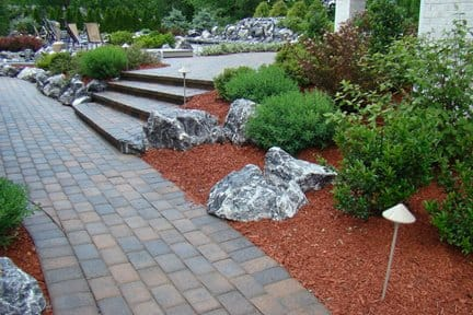 outdoor walkway lined with red mulch