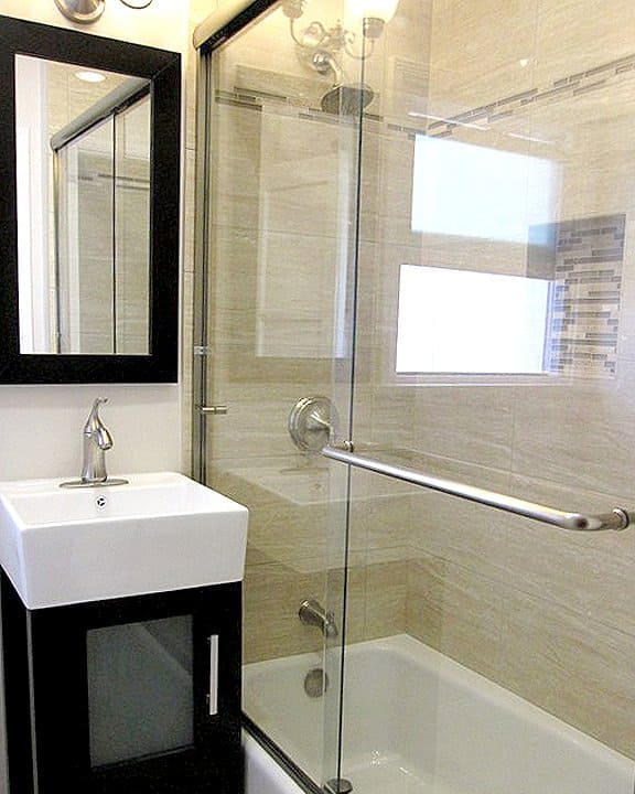 Remodeled Bathroom With Glass Shower Doors And Mirror
