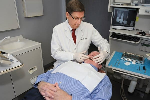 Dr. Kenneth Grundset installed a dental implant and a crown for Norman Cosper last year. (Photo by John Zambito)