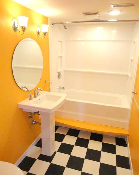 bathroom remodel with yellow walls and checkerboard floor