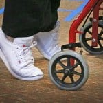 Feet closeup of an elderly woman uses rolling walker to do stretching exercises