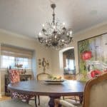 Dining room with ornate chandelier and ceiling wallpaper by artist Walter Knabe
